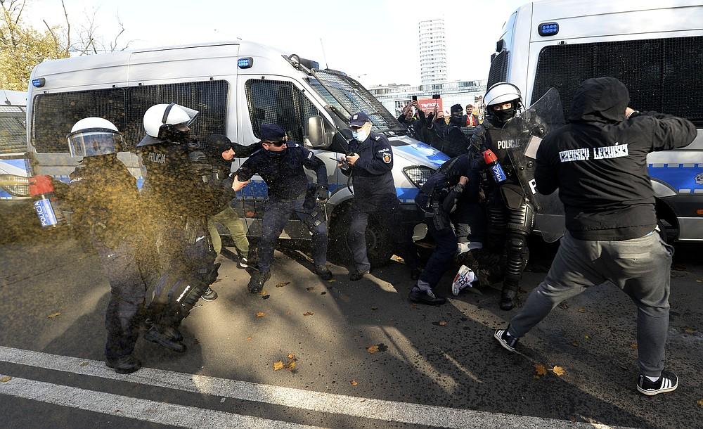 Polish police aim tear gas cannisters at protesters angry over new restrictions aimed at fighting the coronavirus pandemic, in Warsaw, Poland, Saturday, Oct. 24, 2020. The protesters included entrepreneurs, far-right politicians, football fans and vaccine opponents. The protesters, many wearing no protective masks, violated a new restriction on gatherings of more people. The clashes come amid rising social tensions and as new restrictions just short of a full lockdown took effect Saturday. (AP Photo/Czarek Sokolowski)