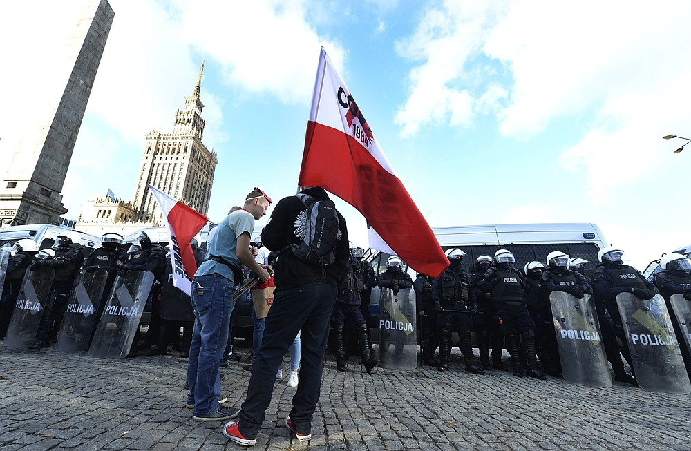 Polish police face protesters angry over new restrictions aimed at fighting the coronavirus pandemic, in Warsaw, Poland, Saturday, Oct. 24, 2020. The protesters included entrepreneurs, far-right politicians, football fans and vaccine opponents. The protesters, many wearing no protective masks, violated a new restriction on gatherings of more people. The clashes come amid rising social tensions and as new restrictions just short of a full lockdown took effect Saturday.(AP Photo/Czarek Sokolowski)
