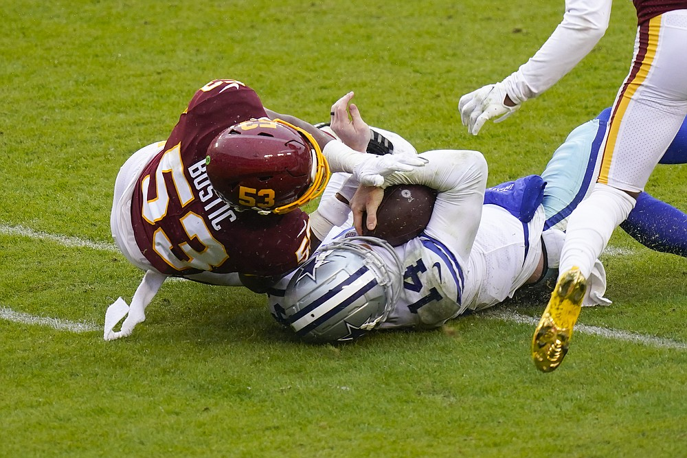 Dallas Cowboys quarterback Andy Dalton (14) collides with Washington Football Team inside linebacker Jon Bostic (53) in the second half of an NFL football game, Sunday, Oct. 25, 2020, in Landover, Md. Dalton left the field after this hit. (AP Photo/Patrick Semansky)