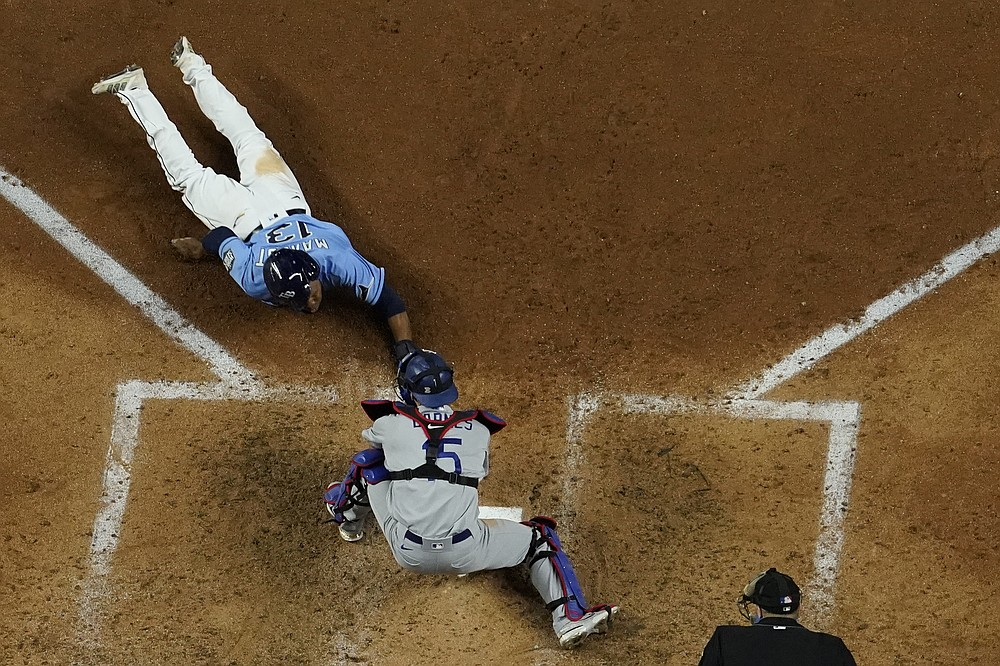 Tampa Bay Rays' Manuel Margot is tagged out at home by Los Angeles Dodgers catcher Austin Barnes trying to steal during the fourth inning in Game 5 of the baseball World Series Sunday, Oct. 25, 2020, in Arlington, Texas. (AP Photo/David J. Phillip)