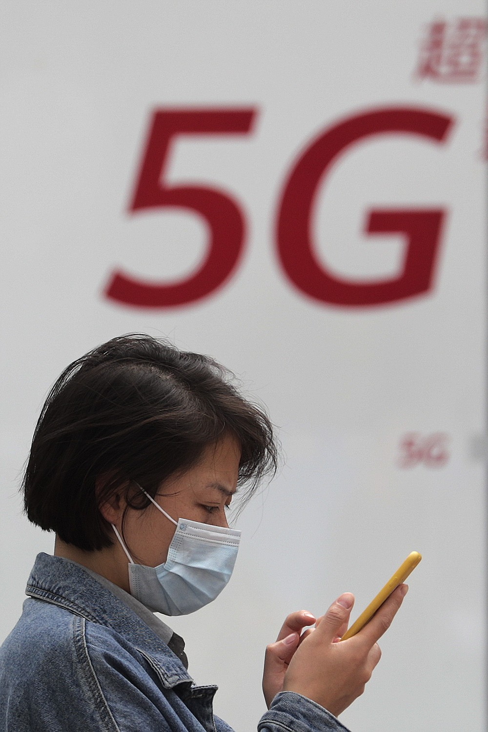A woman wearing a face mask to help curb the spread of the coronavirus browses her smartphone in front of a 5G network advertisement at the Huawei retail shop in Beijing on Oct. 11, 2020. Chinese leaders are meeting to formulate an economic blueprint for the next five years that is expected to emphasize development of semiconductors and other technology amid a feud with Washington that is cutting off access to U.S. components for China's fledgling tech industries. (AP Photo/Andy Wong)