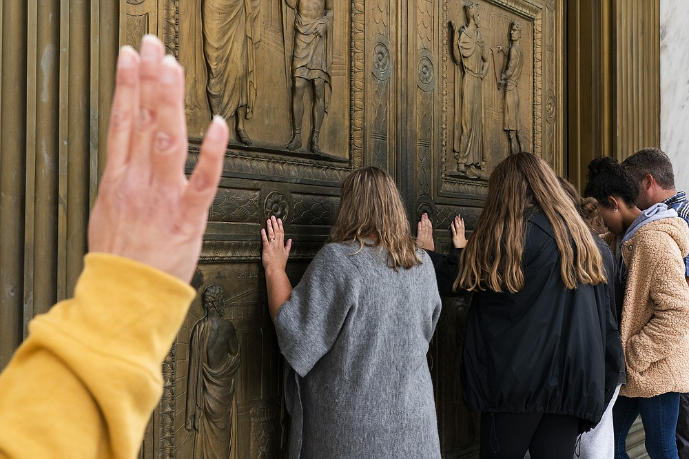 People pray to Jesus at the door of the Supreme Court in support of Supreme Court nominee Amy Coney Barrett, Monday, Oct. 26, 2020, outside the Supreme Court on Capitol Hill in Washington. (AP Photo/Jacquelyn Martin)