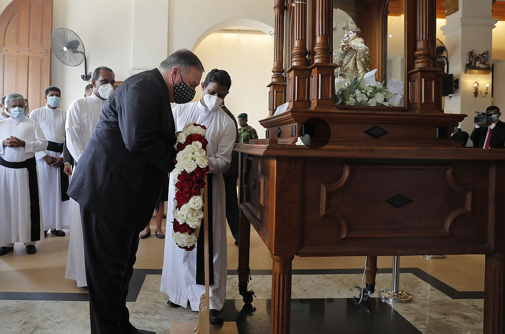 U.S. Secretary of State Mike Pompeo places a wreath of flowers at St. Anthony's church, one of the sites of the 2019 Easter Sunday attacks, in Colombo, Sri Lanka, Wednesday, Oct. 28, 2020. Pompeo plans to press Sri Lanka to push back against Chinese assertiveness, which U.S. officials complain is highlighted by predatory lending and development projects that benefit China more than the presumed recipients. The Chinese Embassy in Sri Lanka denounced Pompeo's visit to the island even before he arrived there, denouncing a senior U.S. official's warning that the country should be wary of Chinese investment. (AP Photo/Eranga Jayawardena, Pool)