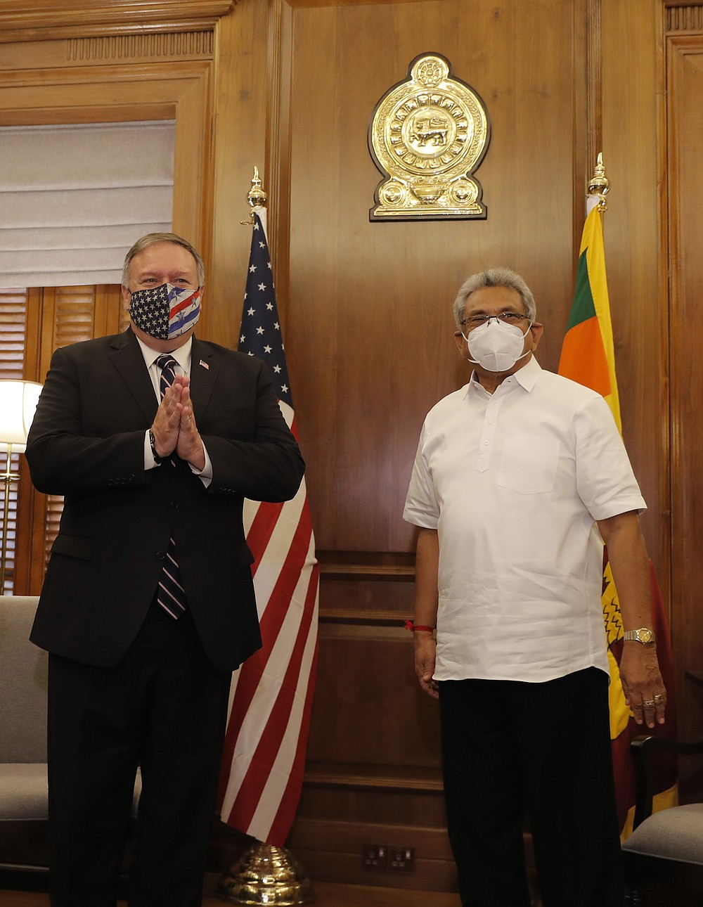 U.S. Secretary of State Mike Pompeo greets the gathering before his meeting with Sri Lankan President Gotabaya Rajapksa in Colombo, Sri Lanka, Wednesday, Oct. 28, 2020. Pompeo plans to press Sri Lanka to push back against Chinese assertiveness, which U.S. officials complain is highlighted by predatory lending and development projects that benefit China more than the presumed recipients. The Chinese Embassy in Sri Lanka denounced Pompeo's visit to the island even before he arrived there, denouncing a senior U.S. official's warning that the country should be wary of Chinese investment. (AP Photo/Eranga Jayawardena, Pool)