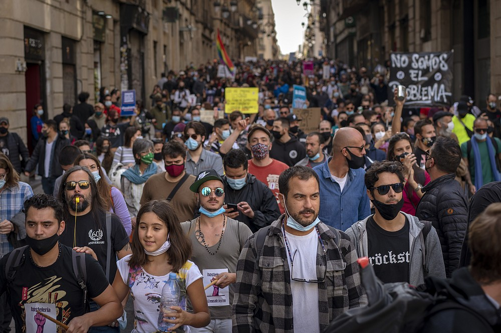 "Workers of several sectors including restaurants, bars, hotel, taxi, and nightclubs march during a protest against the latest virus restrictions in Barcelona, Spain, Wednesday, Oct. 28, 2020. Since Oct. 14 bars and restaurants have been closed, allowed to serve food and drink for take-away and delivery only. On Sunday a curfew from 10p.m. to 6 a.m. was imposed. Still, virus cases are surging and Catalan authorities are now considering even more restrictions including weekend lockdowns. Banner reads in Spanish ""we want to work"". (AP Photo/Emilio Morenatti)"