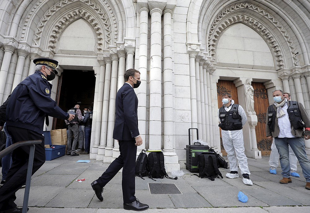 French President Emmanuel Macron, center, arrives at Notre Dame church in Nice, southern France, Thursday, Oct. 29, 2020. An attacker armed with a knife killed at least three people at a church in the Mediterranean city of Nice, prompting the prime minister to announce that France was raising its security alert status to the highest level. It was the third attack in two months in France amid a growing furor in the Muslim world over caricatures of the Prophet Muhammad that were re-published by the satirical newspaper Charlie Hebdo. (Eric Gaillard/Pool via AP)