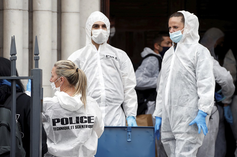 Forensic police officers inspect the scene of a knife attack at Notre Dame church in Nice, southern France, Thursday, Oct. 29, 2020. An attacker armed with a knife killed at least three people at a church in the Mediterranean city of Nice, prompting the prime minister to announce that France was raising its security alert status to the highest level. It was the third attack in two months in France amid a growing furor in the Muslim world over caricatures of the Prophet Muhammad that were re-published by the satirical newspaper Charlie Hebdo. (Eric Gaillard/Pool via AP)