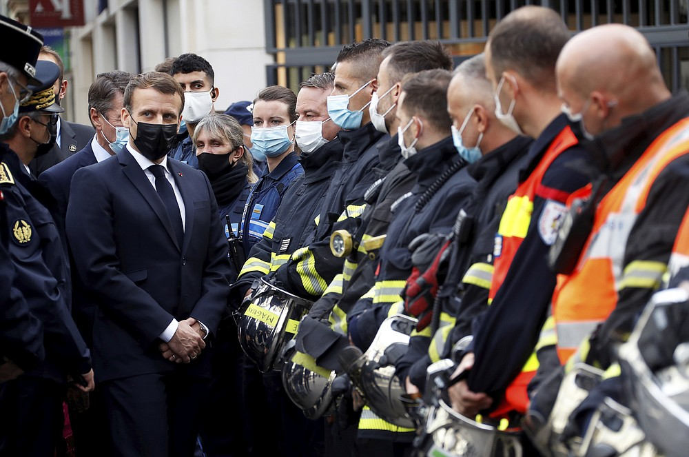French President Emmanuel Macron meets rescue workers after a knife attack at Notre Dame church in Nice, southern France, Thursday, Oct. 29, 2020. An attacker armed with a knife killed at least three people at a church in the Mediterranean city of Nice, prompting the prime minister to announce that France was raising its security alert status to the highest level. It was the third attack in two months in France amid a growing furor in the Muslim world over caricatures of the Prophet Muhammad that were re-published by the satirical newspaper Charlie Hebdo. (Eric Gaillard/Pool via AP)