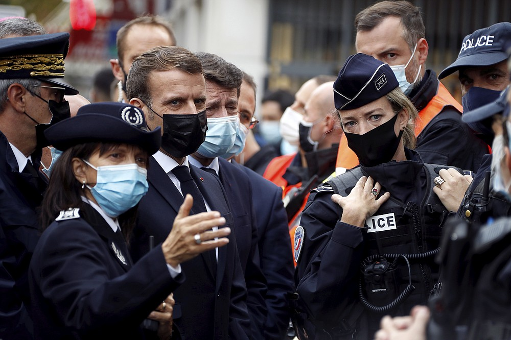 French President Emmanuel Macron, second left, and Nice mayor Christian Estrosi , third left, meet police officers after a knife attack at Notre Dame church in Nice, southern France, Thursday, Oct. 29, 2020. An attacker armed with a knife killed at least three people at a church in the Mediterranean city of Nice, prompting the prime minister to announce that France was raising its security alert status to the highest level. It was the third attack in two months in France amid a growing furor in the Muslim world over caricatures of the Prophet Muhammad that were re-published by the satirical newspaper Charlie Hebdo. (Eric Gaillard/Pool via AP)