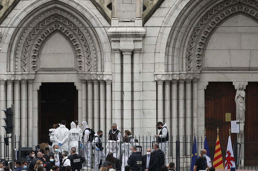 French policemen and forensic officers work on the scene of the knife attack in front of Notre Dame church, in Nice, France, Thursday, Oct. 29, 2020. An attacker armed with a knife killed three people at a church in the Mediterranean city of Nice, the third attack in two months in France. (AP Photo/Daniel Cole)
