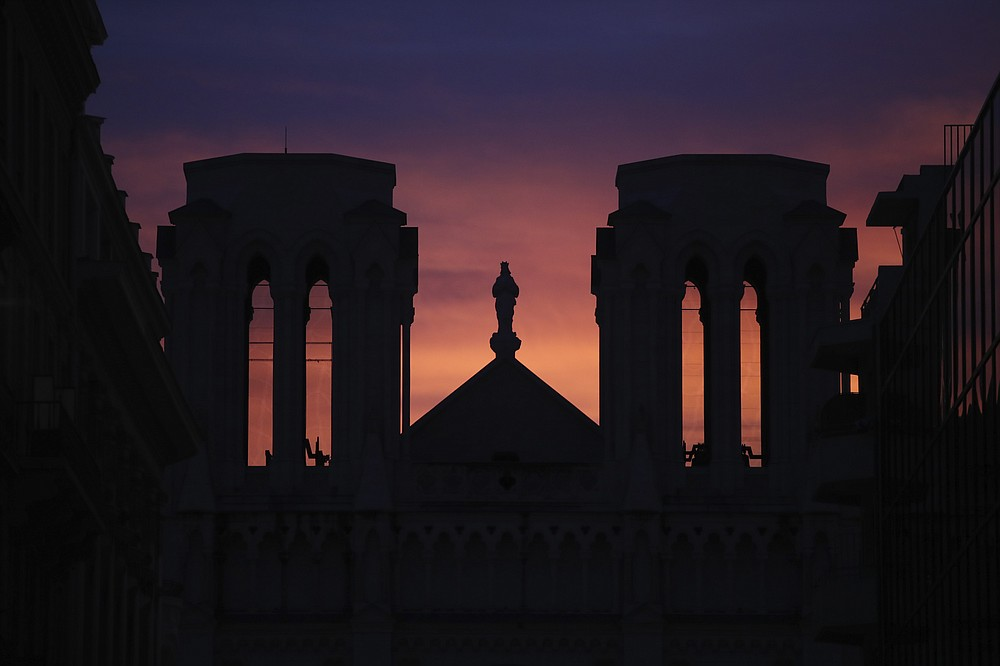 The sun sets behind the Notre Dame church in Nice, southern France, after a knife attack took place on Thursday, Oct. 29, 2020. An attacker armed with a knife killed at least three people at a church in the Mediterranean city of Nice, prompting the prime minister to announce that France was raising its security alert status to the highest level. (AP Photo/Daniel Cole)