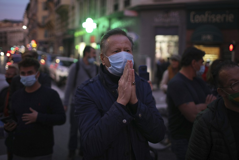 A man prays in the street outside the Notre Dame church in Nice, southern France, after a knife attack took place on Thursday, Oct. 29, 2020. An attacker armed with a knife killed at least three people at a church in the Mediterranean city of Nice, prompting the prime minister to announce that France was raising its security alert status to the highest level. (AP Photo/Daniel Cole)