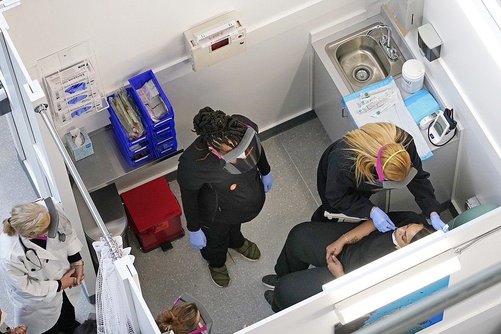 A swab test is administered to a woman at the new XpresCheck COVID-19 testing facility at Boston Logan International Airport, Wednesday, Oct. 28, 2020, in Boston. The testing site is open for airport and airline employees, and will open to passengers and the general public in mid-November. (AP Photo/Elise Amendola)
