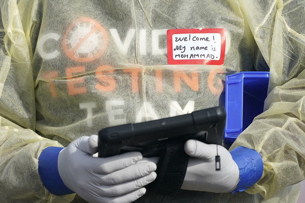 A worker wearing gloves, and other PPE holds a tablet computer as he waits to check people in, Wednesday, Oct. 28, 2020, at a King County coronavirus testing site in Auburn, Wash., south of Seattle. State health officials say that a new COVID-19 report released Wednesday shows an increase in coronavirus cases and hospitalizations throughout Washington state, and if not brought under control, officials said the spike could jeopardize progress toward reopening schools, strain the health care system and increase risks during the holiday season. (AP Photo/Ted S. Warren)