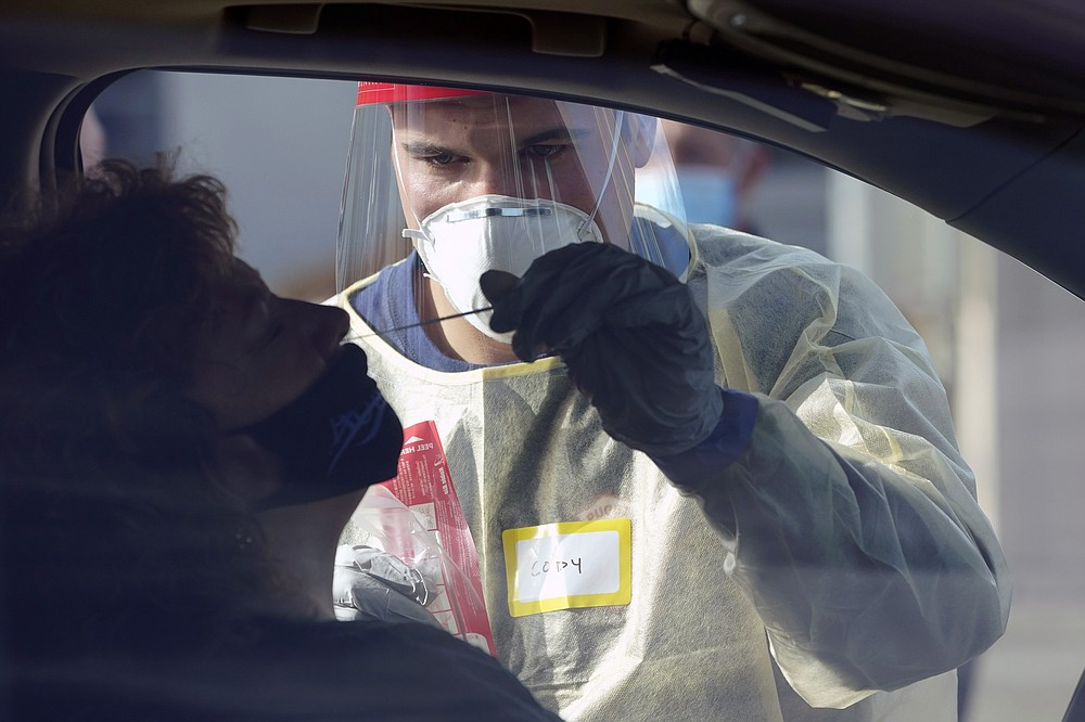 Cody Tupen, a firefighter with the Puget Sound Regional Fire Authority, performs a deep nasal nose-swab COVID-19 test on Nancy Backus, left, the mayor of Auburn, Wash., at a King County COVID-19 testing site in Auburn, south of Seattle, Wednesday, Oct. 28, 2020. State health officials say that a new COVID-19 report released Wednesday shows an increase in coronavirus cases and hospitalizations throughout Washington state, and if not brought under control, officials said the spike could jeopardize progress toward reopening schools, strain the health care system and increase risks during the holiday season. (AP Photo/Ted S. Warren)