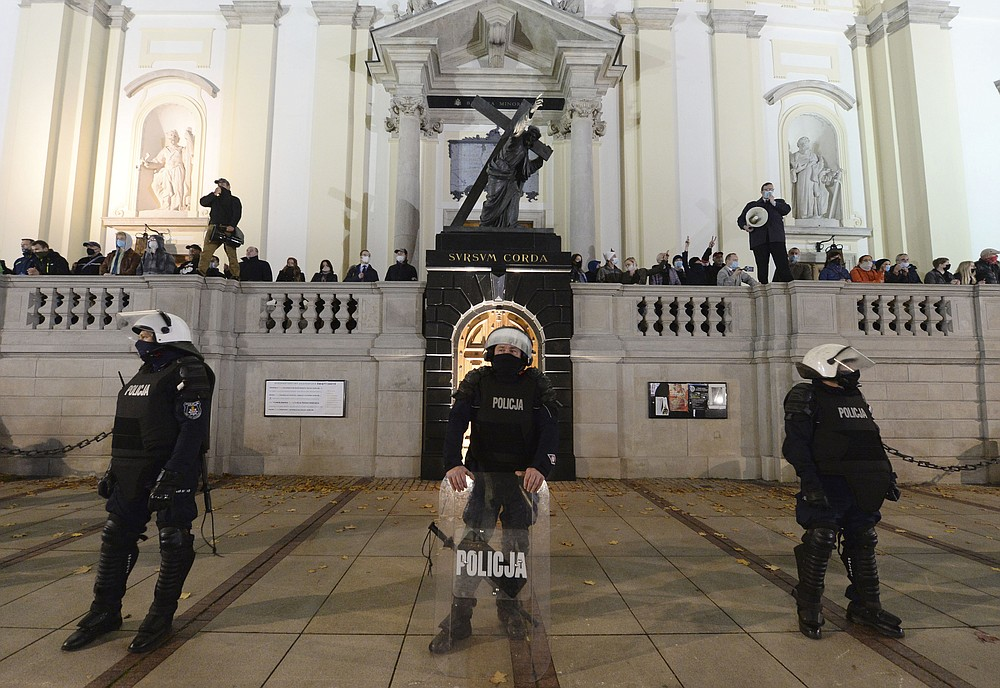 Members of a far-right organization stand guard in front of the Holy Cross Church, fronted by a row of police officers, in Warsaw, Poland, Wednesday Oct. 28, 2020. The far-right group members vowed to defend churches after protesters angry over an abortion ban disrupted Masses and spray-painted churches last Sunday. (AP Photo/Czarek Sokolowski)