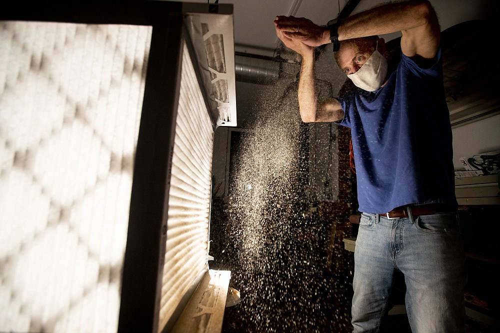 Tom Avril uses sawdust to demonstrates how the air filtering system works. (TNS/Charles Fox/The Philadelphia Inquirer)