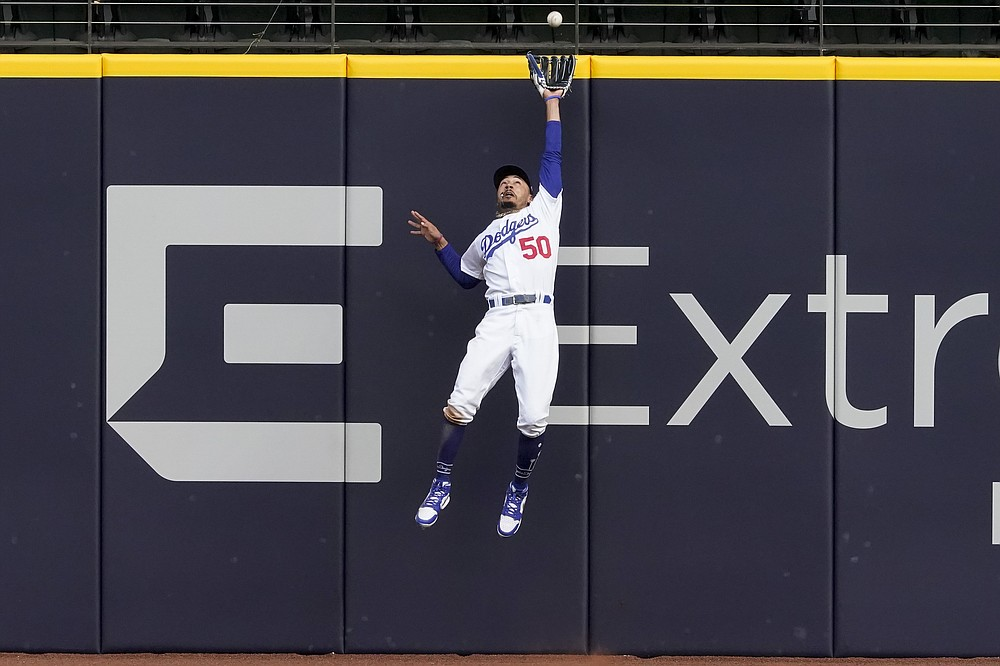 FILE - In this Oct. 17, 2020, file photo, Los Angeles Dodgers right fielder Mookie Betts robs Atlanta Braves' Marcell Ozuna of a home during the fifth inning in Game 6 of a baseball NL Championship Series in Arlington, Texas. Betts won his fifth consecutive Gold Glove on Tuesday, Nov. 3, 2020. (AP Photo/Tony Gutierrez, File)