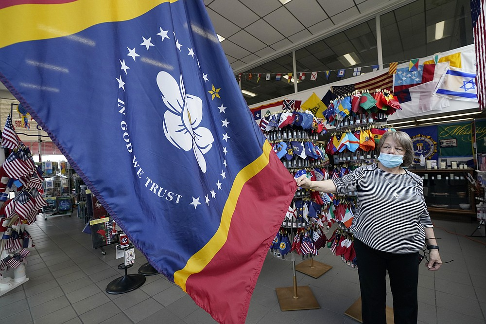 FILE - In this Tuesday, Oct. 27, 2020, file photo, Brenda McIntyre, a co-owner of A Complete Flag Source store in Jackson, Miss., shows off the magnolia-centered banner chosen by the Mississippi State Flag Commission, that voters will vote on as the new Mississippi state flag on Nov. 3, 2020. (AP Photo/Rogelio V. Solis, File)