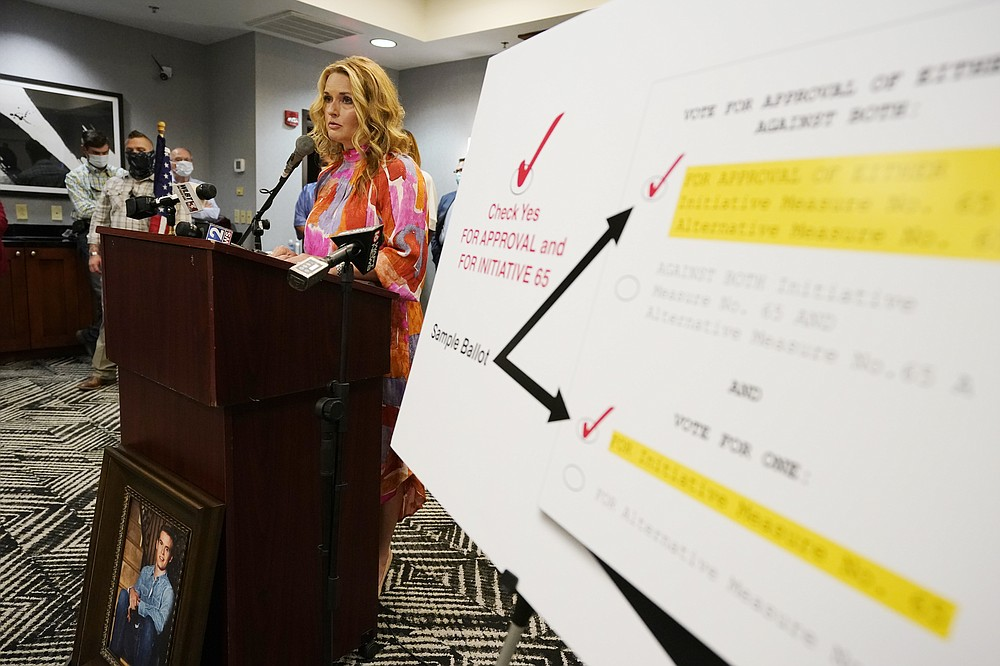 FILE - In this Tuesday, Oct. 27, 2020, file photo, Angie Calhoun of Madison, speaks about her son Austin, in the photo below the lectern, having to move to Colorado when he was 19 for medical marijuana treatment because treatment for his chronic conditions including focal seizures, severe joint pain and nausea then required his taking 17 prescriptions including opioids, during a Initiative 65 rally in Ridgeland, Miss. Initiative 65 would amend the Mississippi Constitution to allow the prescription by a doctor of up to 5 ounces (142 grams) of marijuana per month for people who suffer from more than 20 medical conditions. The state lawmakers are offering a more restrictive measure as an alternative. (AP Photo/Rogelio V. Solis, File)