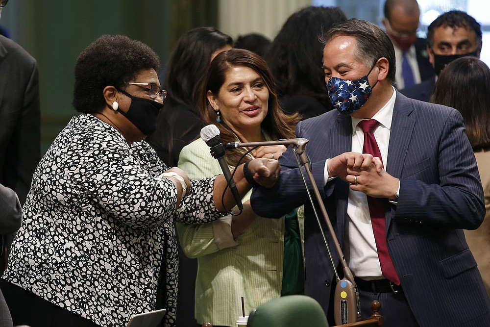 FILE - In this June 10, 2020, file photo, Assemblywoman Shirley Weber, D-San Diego, left, receives congratulations from fellow Assembly members Sharon Quirk-Silva, D-Fullerton, center, and Phil Ting, D-San Francisco, after the Assembly approved her measure to place a constitutional amendment on the Nov. 3, 2020 ballot to let voters decide if the state should overturn its ban on affirmative action programs, at the Capitol in Sacramento, Calif. (AP Photo/Rich Pedroncelli, File)