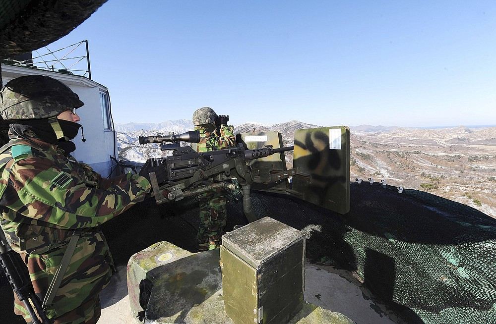 """FILE - In this Dec. 19, 2011, file photo, South Korean army soldiers stand guard after a news reporting about the death of North Korean leader Kim Jong Il at a guard post in the demilitarized zone between South and North Korea in Goseong, South Korea. South Korean troops were engaged in an operation near the heavily fortified border with North Korea on Wednesday, Nov. 4, 2020, after detecting """"unidentified personnel"""" there, the South's military said. (Korea Pool via AP, File)"""
