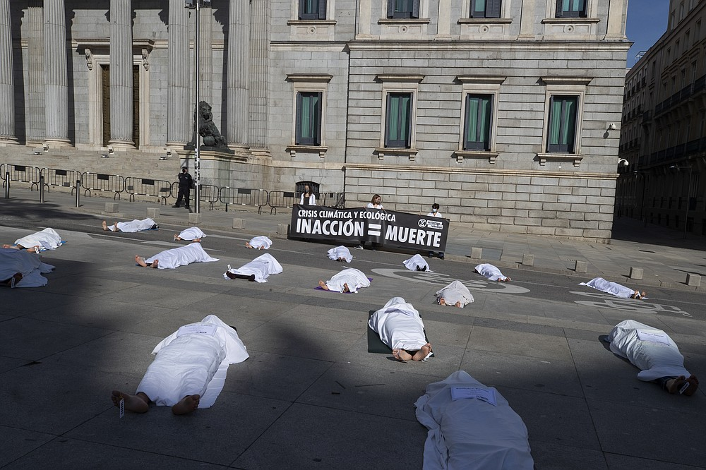 Activists from Extinction Rebellion lie down outside the Spanish parliament during a protest with symbolic corpses coinciding with All Saints' Day, also known as Day of the Dead, Madrid, Spain, Sunday, Nov. 1, 2020. The protest is to call attention to the causes of death related to the climate crisis. Banner reads ' Crisis climate and ecology. Inaction = death'. (AP Photo/Paul White)