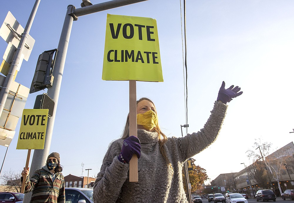 Kristin Green, left, and Kayla Bordelon, from the Citizens Climate Lobby, hold signs and wave to motorists on Election Day, Tuesday, Nov. 3, 2020, in Moscow, Idaho. (Geoff Crimmins/The Moscow-Pullman Daily News via AP)