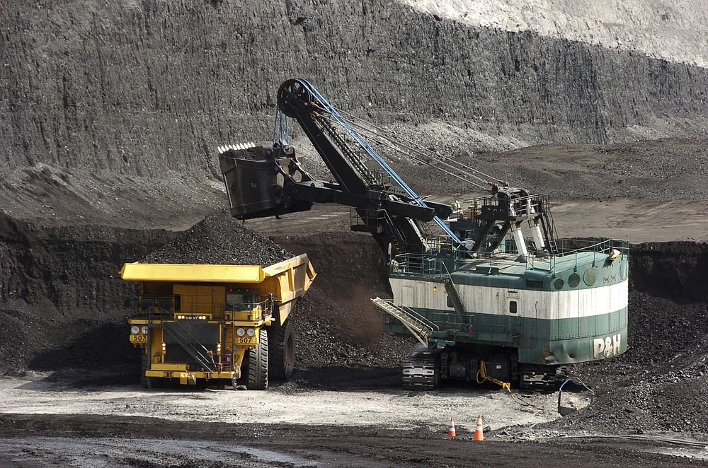FILE - In this April 4, 2013, file photo, a mechanized shovel loads a haul truck with coal at the Spring Creek coal mine near Decker, Mont. The United States is out of the Paris climate agreement on the day after the 2020 presidential election. Experts say the outcome will determine to some degree just how hot and nasty the world will get in the future. The two presidential candidates have stark differences on fighting human-caused climate change.  (AP Photo/Matthew Brown, File)