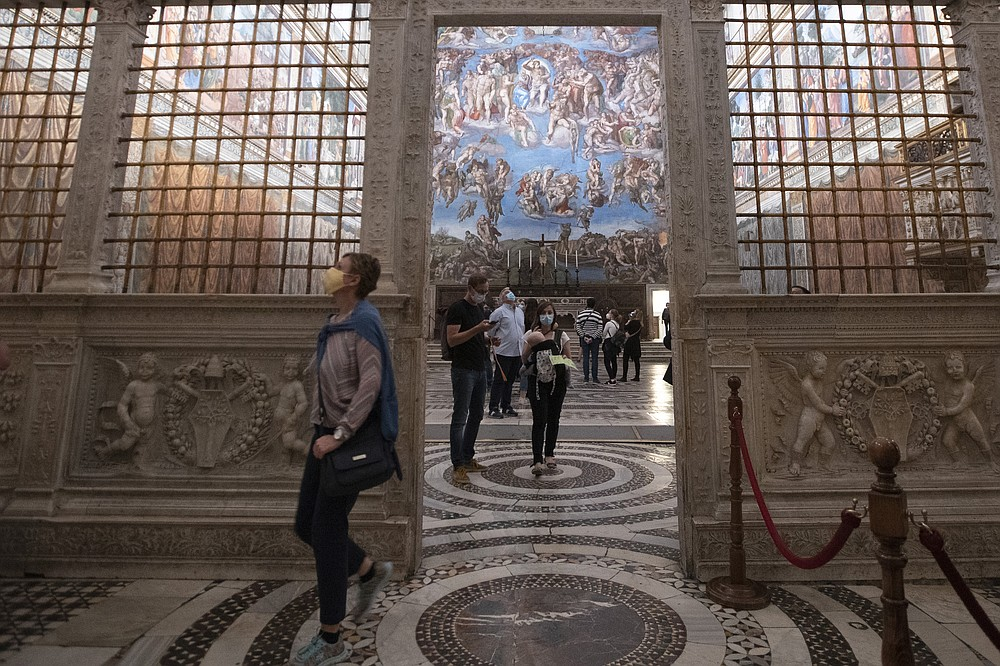 FILE - In this June 1, 2020 file photo, visitors admire the Sistine Chapel as the Vatican Museum reopened, in Rome. Francis urged people follow recommendations from governments and health authorities to prevent coronavirus infections as on Wednesday, Nov. 4, 2020 he returned to his private library for his general audience amid a surge of infections in Europe, and in another sign that the Vatican was reentering into a semi-lockdown mode again, the Holy See announced that it was shuttering the Vatican Museums and the Sistine Chapel to the public until at least Dec. 3. (AP Photo/Alessandra Tarantino, file)