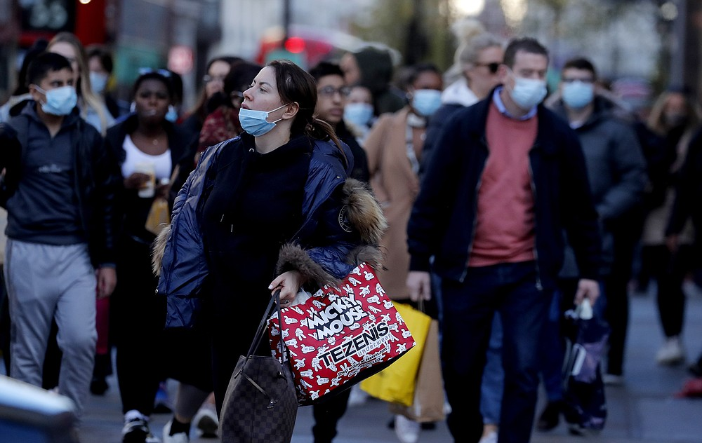 Shoppers walk along a very busy Regent Street in London, Wednesday, Nov. 4, 2020, as Britain prepared to join large swathes of Europe in a coronavirus lockdown designed to save its health care system from being overwhelmed. Pubs, along with restaurants, hairdressers and shops selling non-essential items will have to close Thursday until at least Dec. 2. (AP Photo/Frank Augstein)