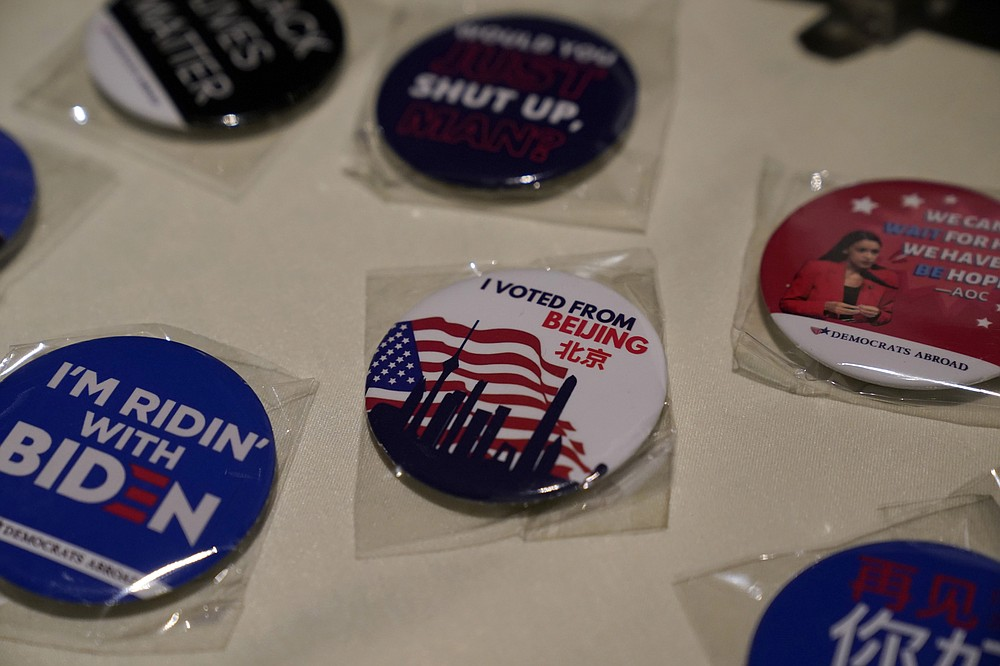 Badges are displayed at an election watch event held by Democrats Abroad at a restaurant in Beijing, China on Wednesday, Nov. 4, 2020. President Donald Trump and his Democratic challenger, Joe Biden, are in a tight battle for the White House. (AP Photo/Ng Han Guan)