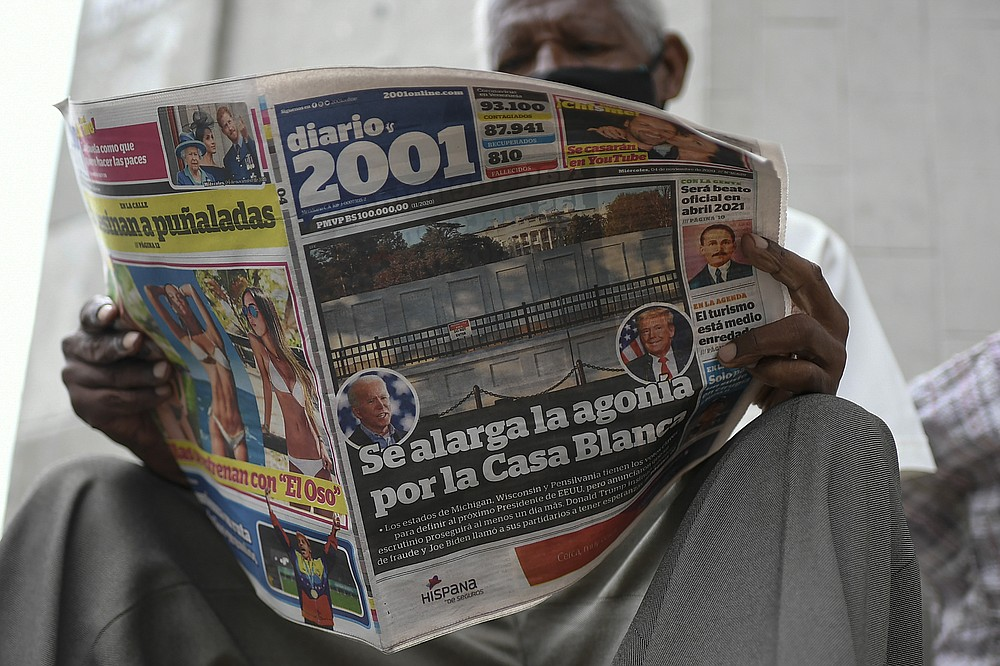 """A man reads the Diario 2001 newspaper that carries the Spanish headline: """"Agony is prolonged for the White House"""" at a newspaper stand in Caracas, Venezuela, Wednesday, Nov. 4, 2020, the day after U.S. elections. (AP Photo/Matias Delacroix)"""