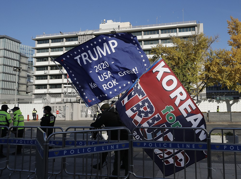 South Korean supporters of U.S. President Donald Trump hold flags near the U.S. Embassy in Seoul, South Korea, Wednesday, Nov. 4, 2020. (AP Photo/Lee Jin-man)