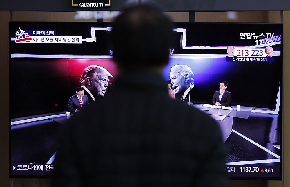 A man watches a TV screen showing the images of U.S. President Donald Trump and Democratic presidential candidate former Vice President Joe Biden during a news program of the U.S. presidential election, at the Seoul Railway Station in Seoul, South Korea, Wednesday, Nov. 4, 2020. (AP Photo/Lee Jin-man)