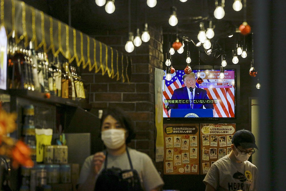 President Donald Trump speaking from the White House is projected on a television at a restaurant Wednesday, Nov. 4, 2020 in Tokyo. (AP Photo/Kiichiro Sato)