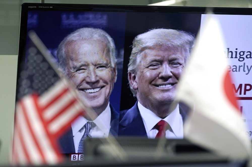 A Japanese and a U.S. flags are placed in front of a TV monitor showing a news program live broadcasting on the U.S. presidential election between President Donald Trump, right, and former Vice President Joe Biden, left, at a foreign exchange dealing company Wednesday, Nov. 4, 2020, in Tokyo. (AP Photo/Eugene Hoshiko)