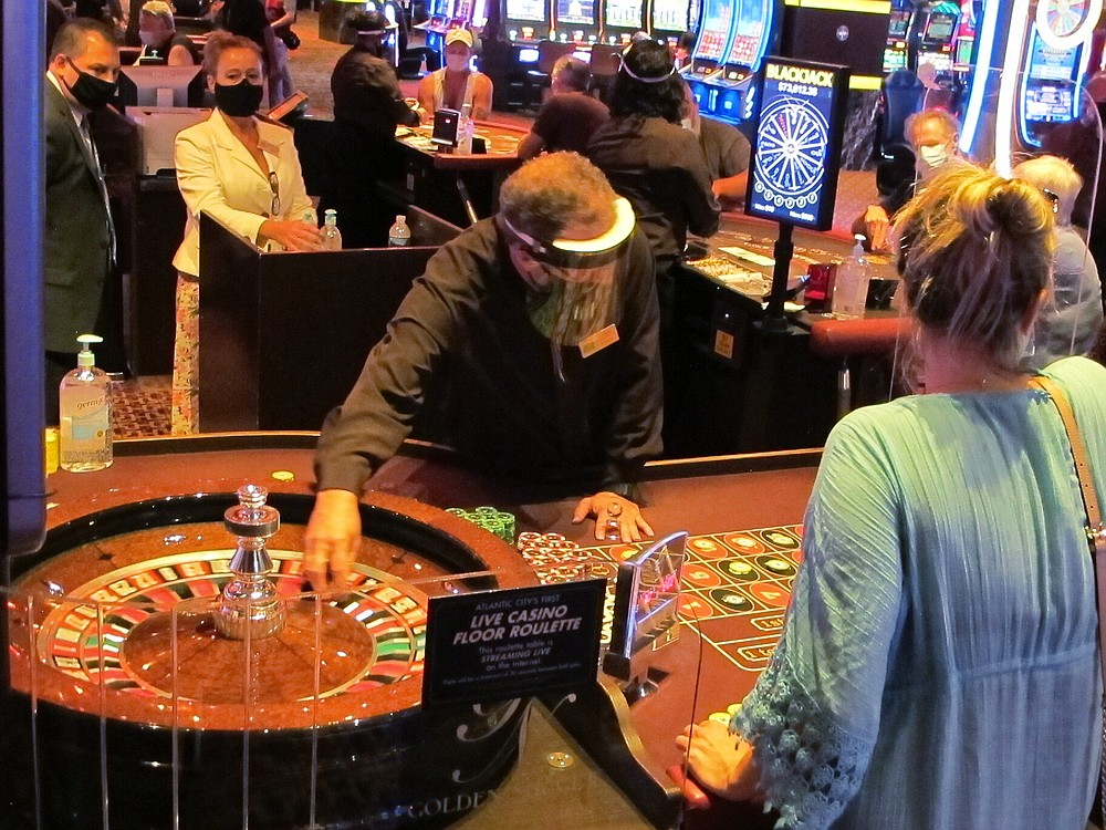 Wearing a face shield to guard against the coronavirus, a dealer conducts a roulette game at the Golden Nugget casino in Atlantic City, N.J. on July 2, 2020. The U.S. gambling industry was a big winner at the polls on Nov. 3, 2020, with three states authorizing sports betting and three others either authorizing or expanding casino gambling. Maryland, South Dakota and Louisiana approved sports betting. (AP Photo/Wayne Parry)