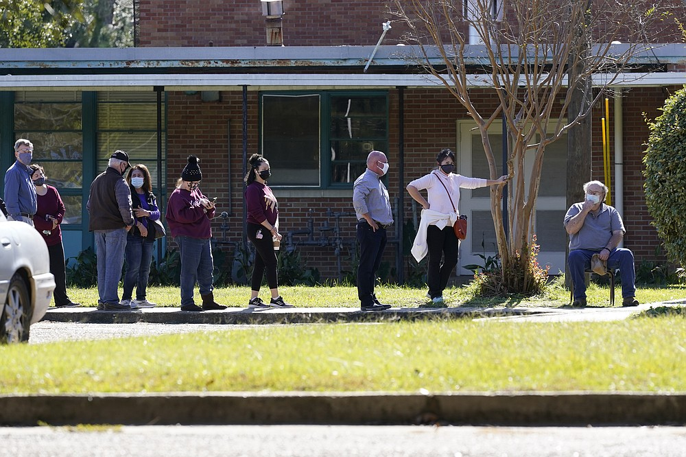 Voters take advantage of an awning to provide them shade while they wait to cast their ballot at Precinct 45 in Jackson, Miss., Tuesday, Nov. 3, 2020. (AP Photo/Rogelio V. Solis)