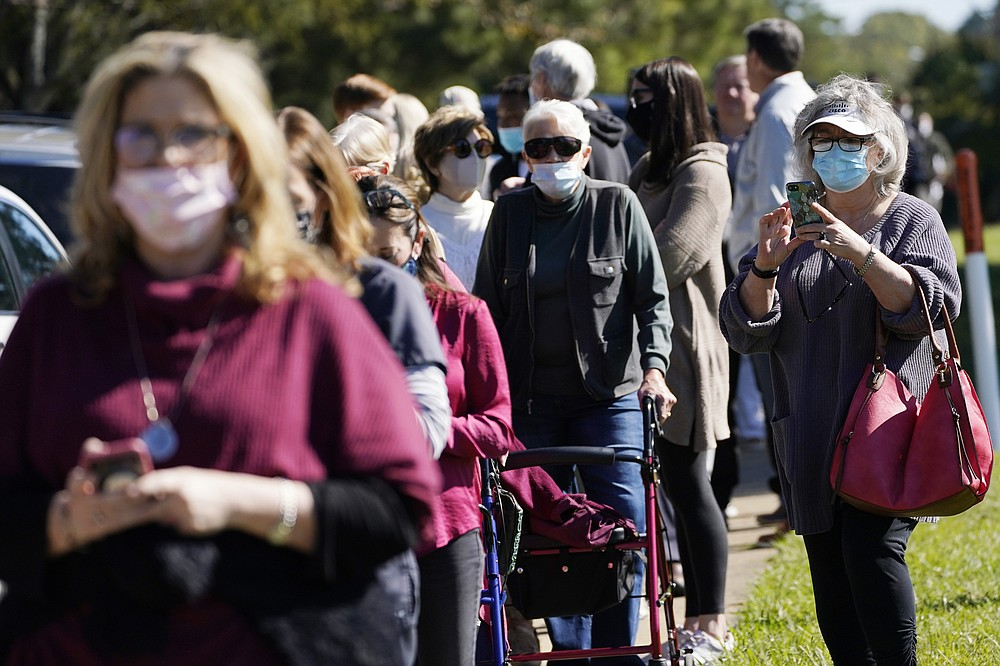 A voter records the long line of people waiting to cast their ballot at Precinct 45 in Jackson, Miss., Tuesday, Nov. 3, 2020. (AP Photo/Rogelio V. Solis)