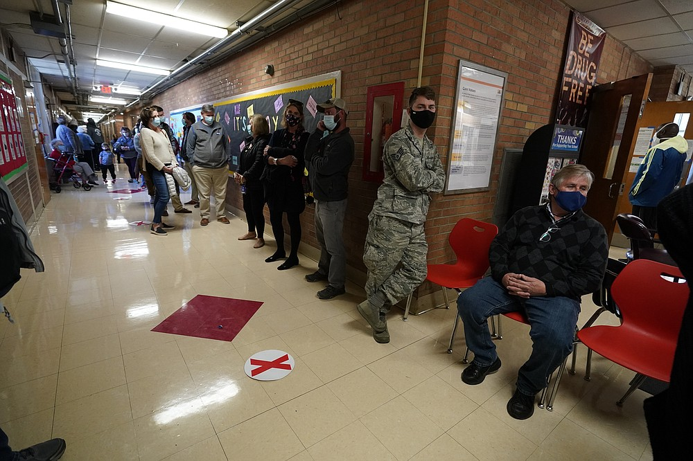 After standing outdoors in line for a couple of hours as they waited their turn to vote, these voters finally made it indoors to the entrance of Precinct 45 where they would cast their votes on Election Day in Jackson, Miss., Tuesday, Nov. 3, 2020. (AP Photo/Rogelio V. Solis)