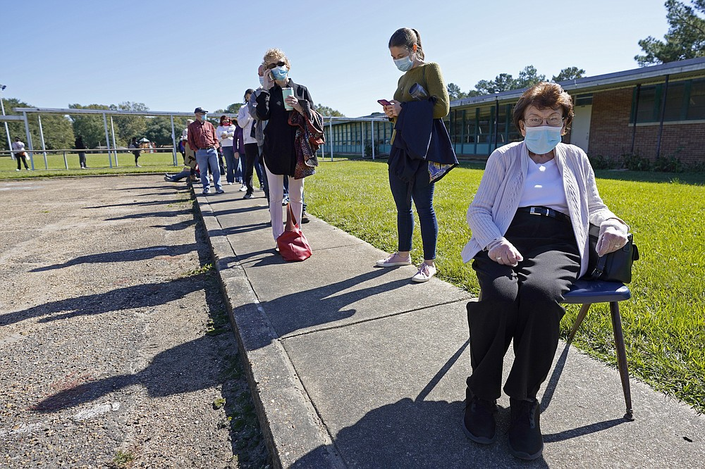 "Nancy Cross admitted to feeling guilty to ""borrowing"" a chair from the student pick up line outside McLeod Elementary School as she waited in line to vote for over two hours to cast her ballot in the general election in Jackson, Miss., Tuesday, Nov. 3, 2020. (AP Photo/Rogelio V. Solis)"