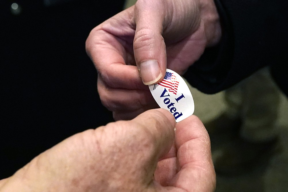 "Election worker Bubba Wright, left, hands out ""I Voted"" stickers to voters on Election Day as they leave a Ridgeland, Miss., precinct Tuesday, Nov. 3, 2020. (AP Photo/Rogelio V. Solis)"