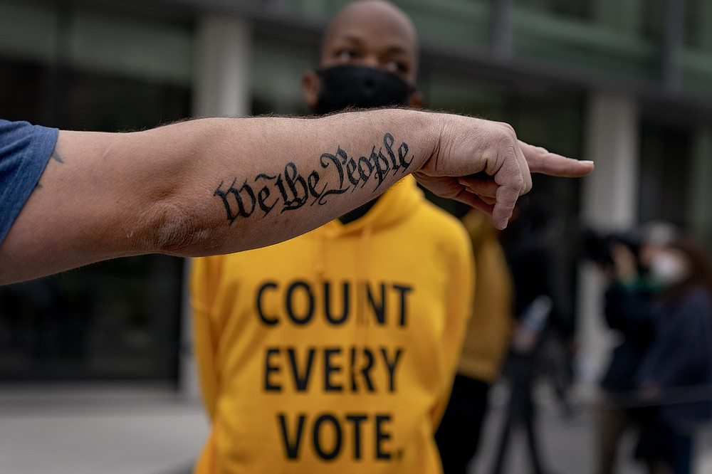 """The tattoo """"We The People"""", a phrase from the United States Constitution, decorates the arm of Trump supporter Bob Lewis, left, as he argues with counter protestor Ralph Gaines while Trump supporters demonstrate against the election results outside the central counting board at the tcf Center in Detroit, Thursday, Nov. 5, 2020. (AP Photo/David Goldman)"""