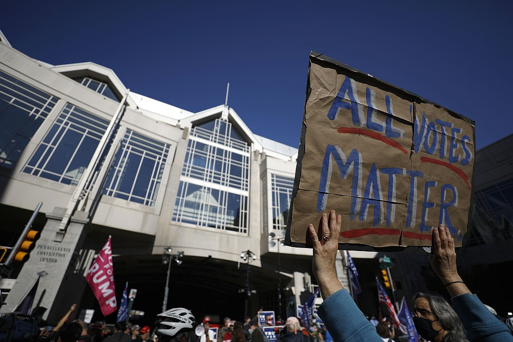 People demonstrate outside the Pennsylvania Convention Center where votes are being counted, Friday, Nov. 6, 2020, in Philadelphia. (AP Photo/Rebecca Blackwell)