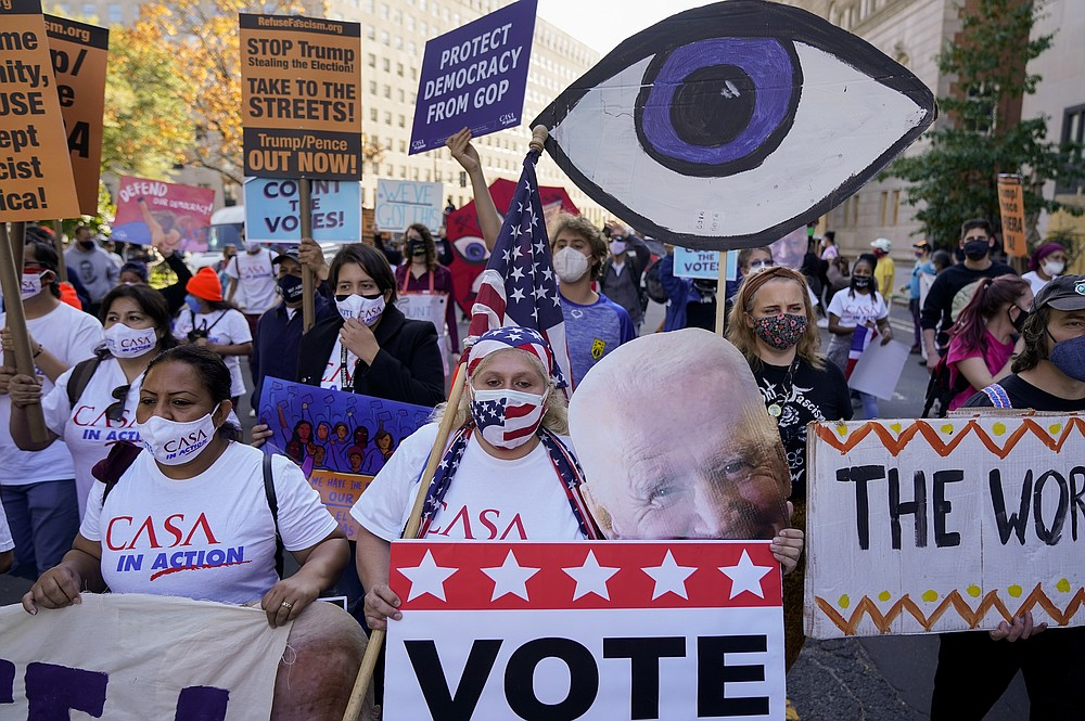 Protestors march through Black Lives Matter Plaza during a Count Every Vote rally, Friday, Nov. 6, 2020, in Washington. (AP Photo/Jacquelyn Martin)