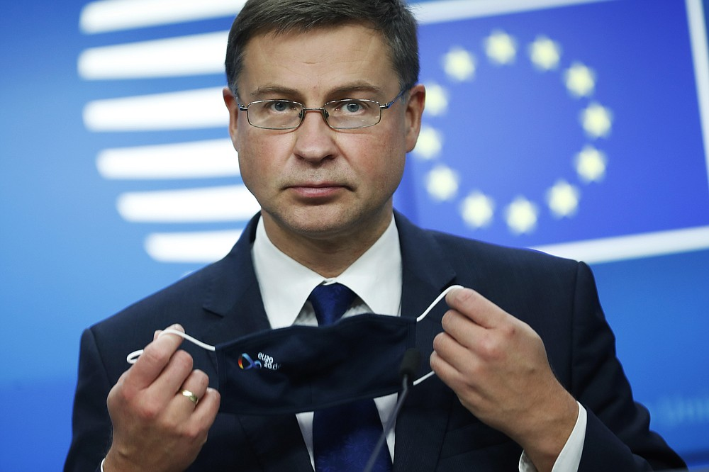 European Commission Vice-President Valdis Dombrovskis takes off his protective face mask prior to addressing a media conference after a meeting of EU trade ministers, in videoconference format, at the European Council building in Brussels, Monday, Nov. 9, 2020. European Union trade ministers on Monday exchanged views on the trade policy review and relations with China and the United States. (AP Photo/Francisco Seco, Pool)