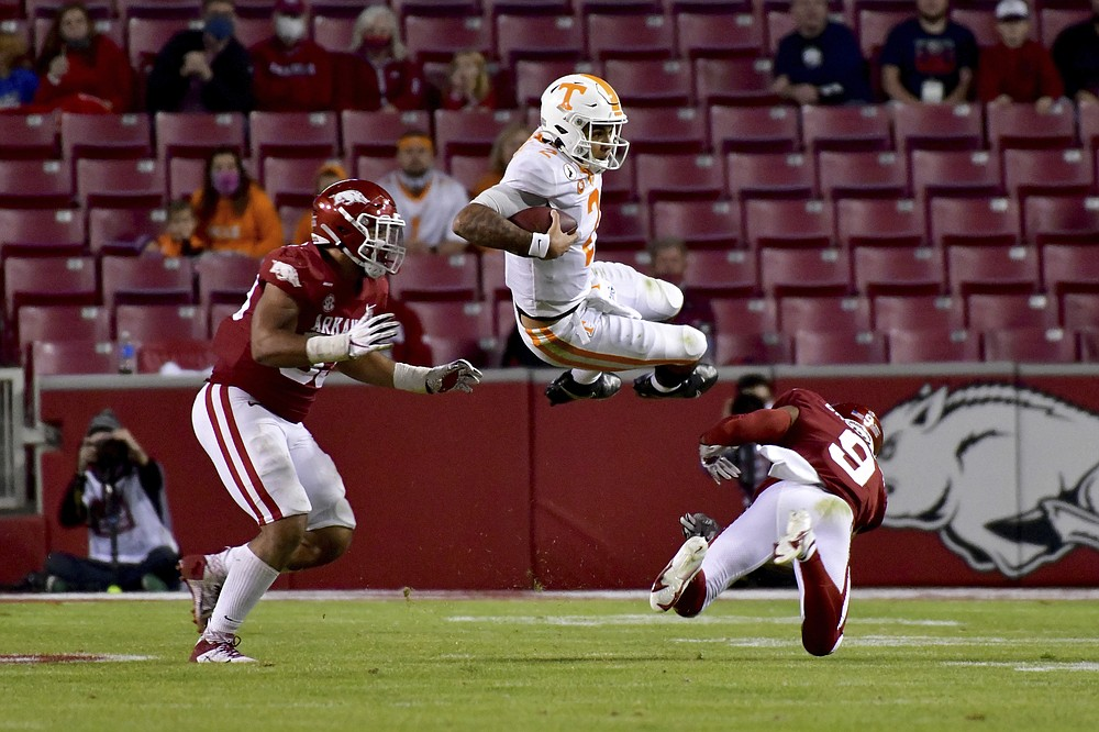 Tennessee quarterback Jarrett Guarantano (2) is tackled by Arkansas defenders Isaiah Nichols, left, and Greg Brooks Jr. during the second half of an NCAA college football game Saturday, Nov. 7, 2020, in Fayetteville, Ark. (AP Photo/Michael Woods)