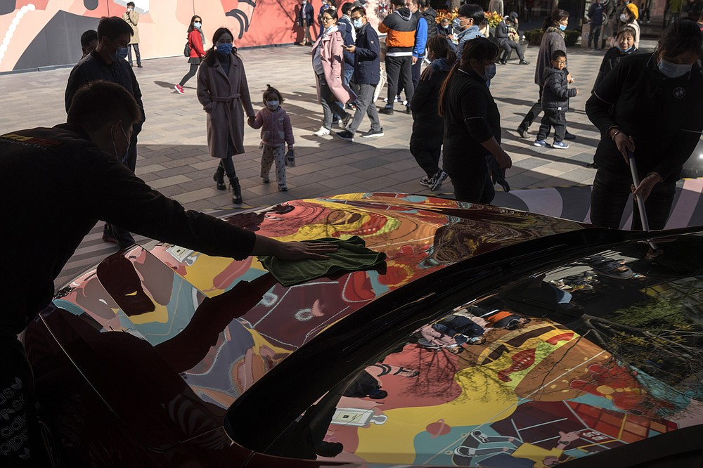 A worker wipes the surface of a luxury car as shoppers wearing mask to protect from the coronavirus visit a shopping district in Beijing on Sunday, Nov. 8, 2020. Chinese consumers are expected to spend tens of billions on everything from fresh food to luxury goods during this year's Singles' Day online shopping festival, as the country recovers from the coronavirus pandemic. (AP Photo/Ng Han Guan)