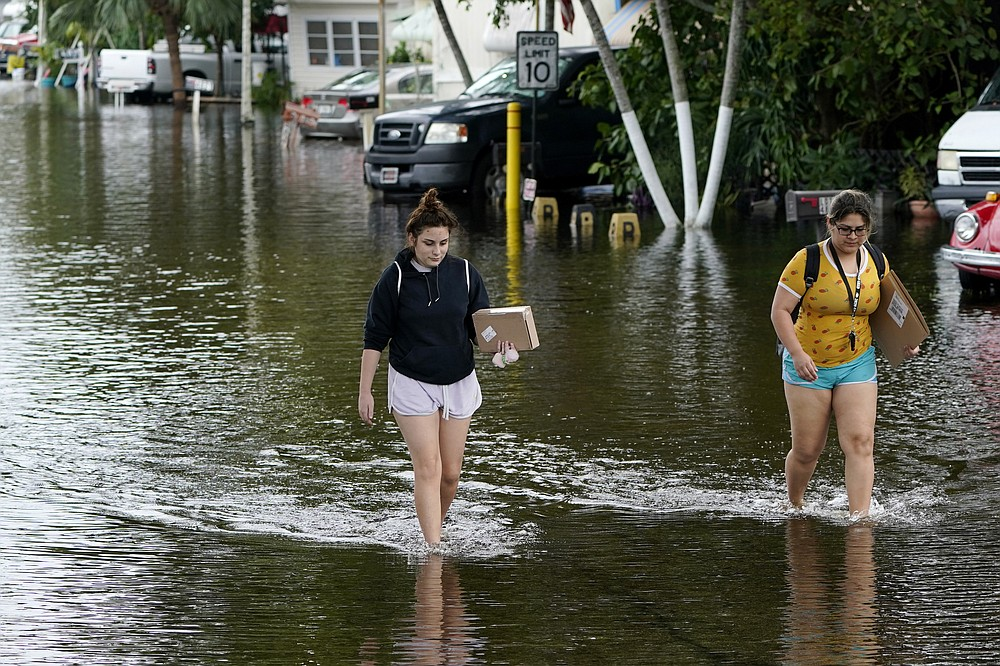 Victoria Rodriguez, left, and Angela Mojica, right, walk on a flooded street in the Driftwood Acres Mobile Home Park, in the aftermath of Tropical Storm Eta, Tuesday, Nov. 10, 2020, in Davie, Fla. Tropical Storm Eta was squatting off western Cuba on Tuesday after drifting away from South Florida, where it unleashed a deluge that flooded entire neighborhoods and covered the floors of some homes and businesses. (AP Photo/Lynne Sladky)